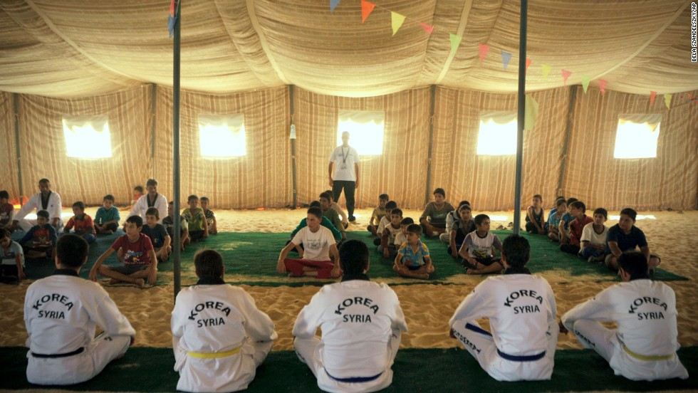 Syrian refugee children watch Korean and Syrian taekwondo instructors during training at the Zaatari refugee camp in Jordan in September 2013.