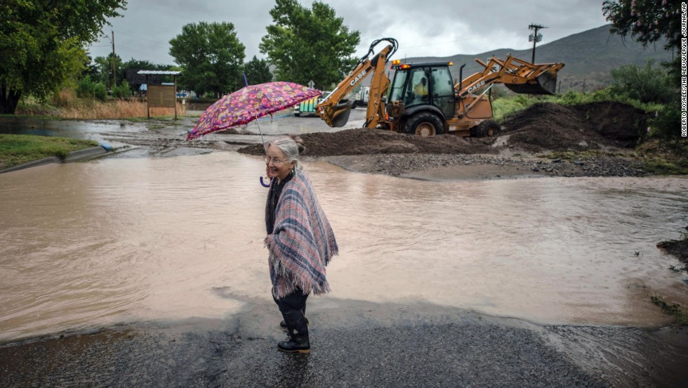Candie Browne dips her boot in water to clean off the mud as a backhoe in the background builds a levy to redirect rainwater from flooding a park near downtown Truth or Consequences, New Mexico, on Friday, September 13.