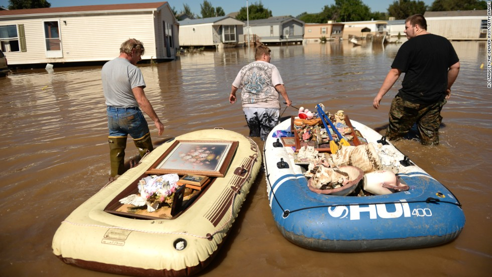 From left, Dale Reeves, Kathryn Reeves and Trent Mayes assist a family member by moving belongings from a flooded home in Evans, Colorado, on September 17.