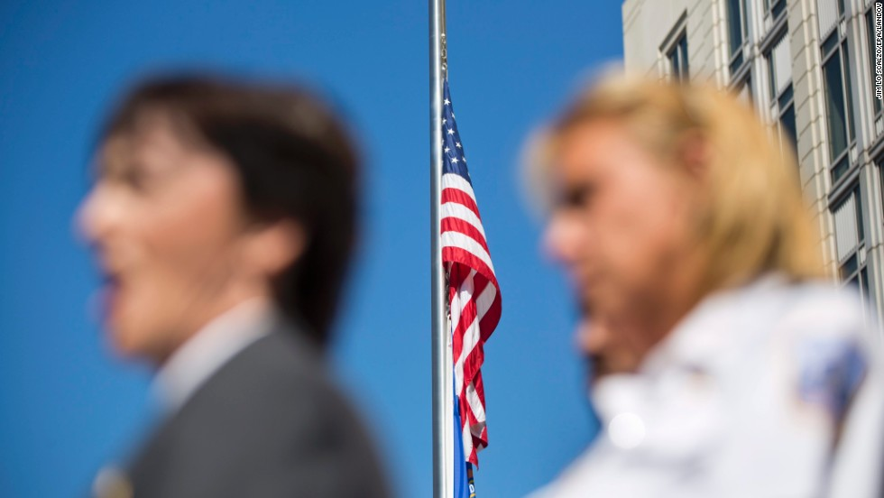 A flag flies at half-staff behind Valerie Parlave of the FBI and Washington Police Chief Cathy Lanier during a press conference on September 17 outside the FBI's field office in Washington.