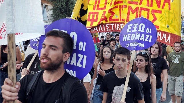 "Anti-fascist protesters hold signs reading ""Neo-Nazis Out"" at a rally in Athens on Wednesday."