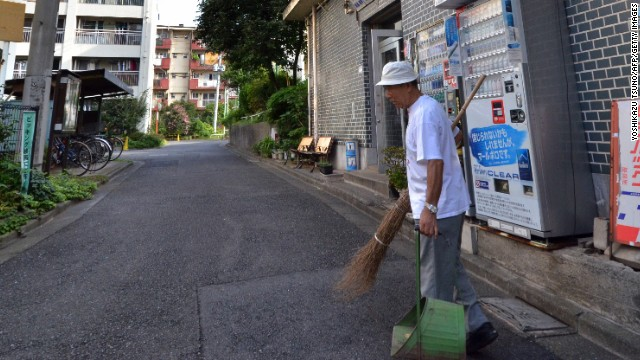 In this picture taken on September 14, 2013, 79-year-old resident Kohei Jinno sweeps and cleans a road before his apartment complex near the rebuilt national stadium in Tokyo. Tokyo's successful bid to host the Olympics made much of plans to re-use venues built for Japan's last Summer Games. But for Kohei Jinno, redevelopment for 2020 means eviction again, just like for 1964. In 1964, his home and business were torn down to make way for an Olympic park around the main stadium for the Tokyo Games. Now he has been told he must move again to make way for the stadium's redevelopment and expansion in time for 2020. AFP PHOTO / Yoshikazu TSUNO (Photo credit should read YOSHIKAZU TSUNO/AFP/Getty Images)