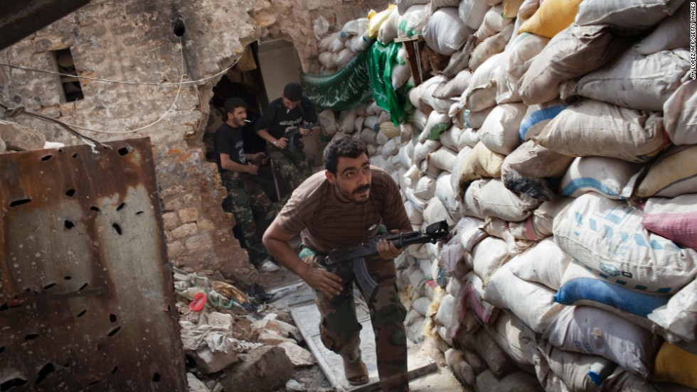Rebel fighters duck behind a barricade from firing in Aleppo on Wednesday, September 18.
