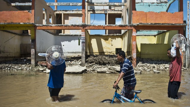 Locals wade through a flooded street in Acapulco, on Wednesday, September 18.