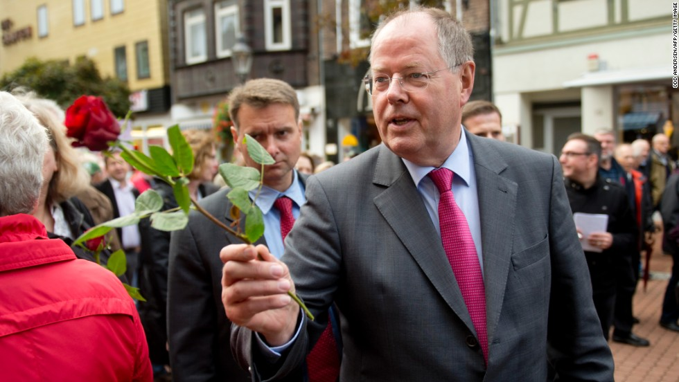 "Peer Steinbrueck, the social democrat Chancellor candidate and<a href=""http://www.cnn.com/2013/09/20/world/europe/germany-merkel-profile/index.html?hpt=hp_c1""> Angela Merkel</a>'s main challenger, hands out roses to well-wishers in German town of Peine on September 16, 2013."