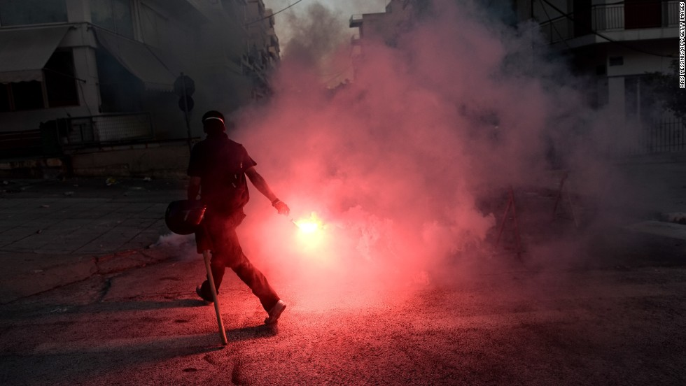 A protestor lights a flare as anti-fascist demonstrators clash with riot police in Athens on September 18, 2013.