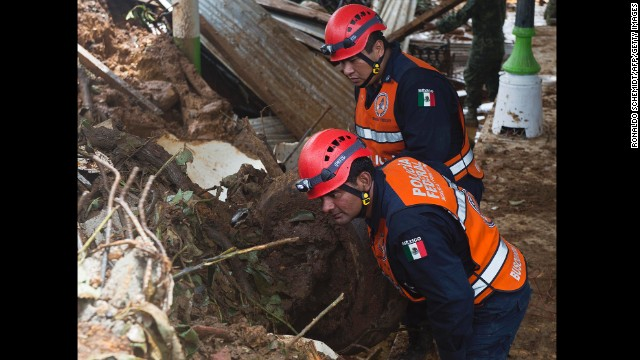 Federal Police officers search for bodies on the site of the landslide in La Pintada, Mexico, on September 19.