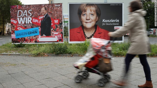 A woman pushes a stroller past election campaign posters for Angela Merkel and Peer Steinbrueck on September 16, 2013 in Berlin, Germany.