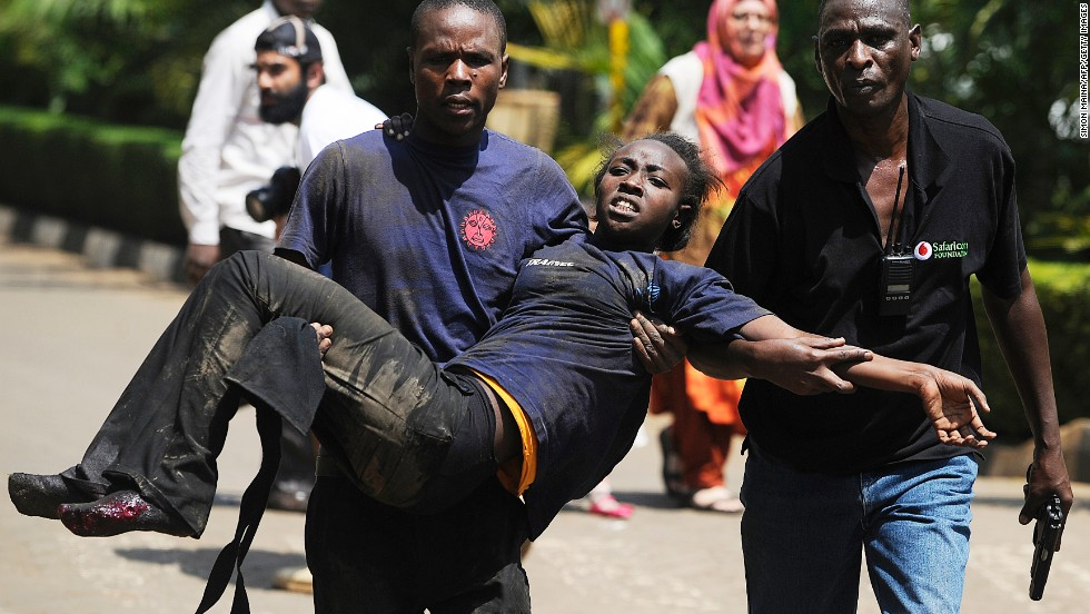 A Kenyan woman is helped to safety after the masked gunmen stormed the upscale mall and sprayed gunfire on shoppers and staff.