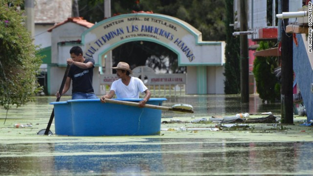 Villagers use a small fiberglass swimming pool as a boat with makeshift oars to transport themselves through flooded streets in the town of Tixtla de Guerrero, Mexico, Sunday, Sept. 22, 2013. Tropical Storm Manuel and Ingrid affected 24 of Mexico's 31 states and 371 municipalities, which are the equivalent of counties. More than 58,000 people were evacuated, with 43,000 taken to shelters. Nearly 1,000 donation centers have been set up around the country, with nearly 700 tons of aid delivered so far.  (AP Photo/Alejandrino Gonzalez)