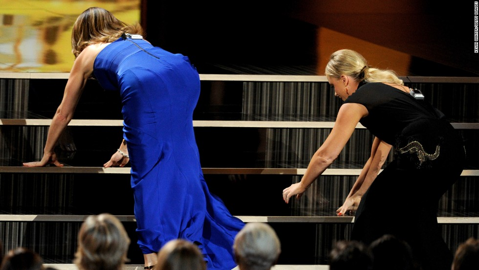 Presenters Tina Fey, left, and Amy Poehler scramble to the stage.