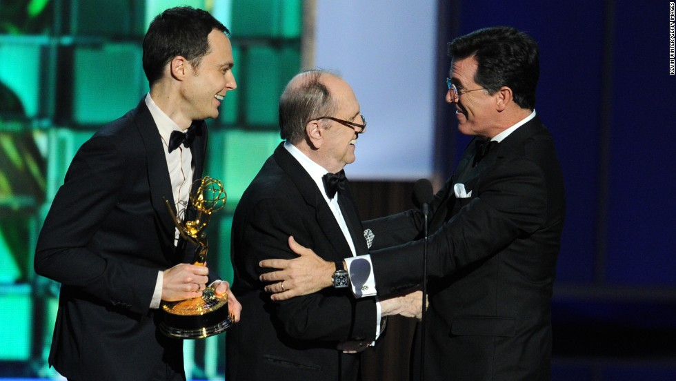 Actors Jim Parsons, left, and Bob Newhart present an award to Stephen Colbert. His show won outstanding variety series and outstanding writing for a variety series.