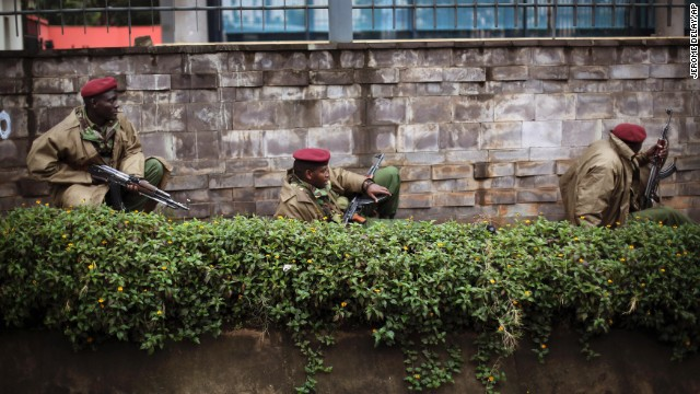 Kenya security forces crouch behind a wall outside the Westgate Mall in Nairobi, Kenya, on Monday, September 23.