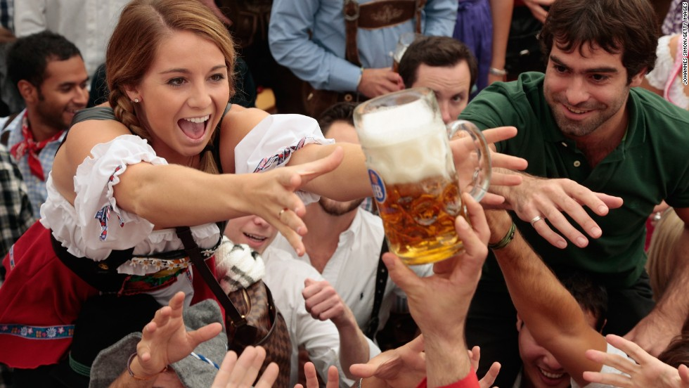 Revelers reach for the first beer mug at the Hofbraeuhaus beer tent during the first day of Oktoberfest, Saturday, September 21.