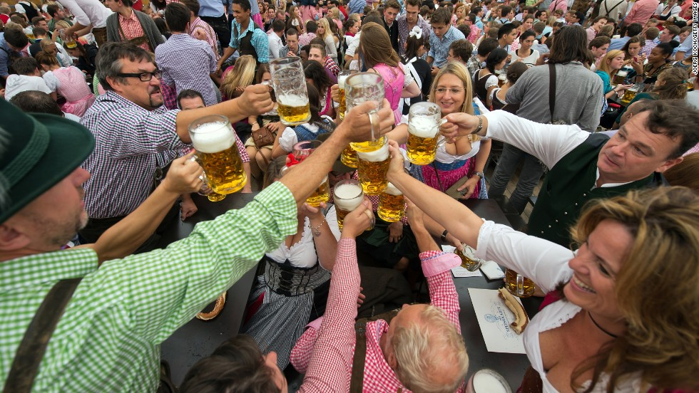People raise their glasses after getting their first beer of Oktoberfest.