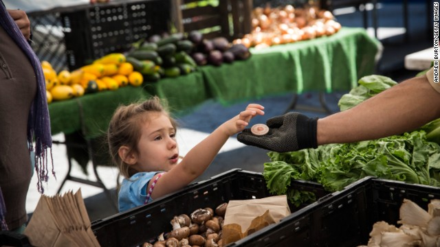 A girl pays for her mom's groceries with a food stamp token at a market in New York's Union Square last week.