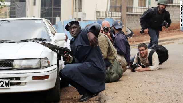 Kenyan security personnel and journalists duck behind a vehicle as heavy gunfire erupts from the Westgate Mall in Nairobi Kenya Monday Sept. 23 2013. Multiple large blasts have rocked the mall where a hostage siege is in its third day. Associated Press reporters on the scene heard multiple blasts and a barrage of gunfire. Security forces have been attempting to rescue an unknown number of hostages inside the mall held by al-Qaida-linked terrorists. (AP Photo/ Jerome Delay) )
