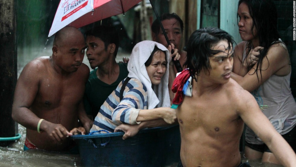 Filipino residents rescue a woman from rising floodwaters in Las Pinas City, Philippines, on Monday, September 23.  More than a dozen people were killed in the Philippines on Monday as heavy rains from Typhoon Usagi battered the main island of Luzon. The storm forced the relocation of hundreds of thousands of people, the cancellation of hundreds of flights and the closing of a major shipping lane. Also, at least 25 people are reported killed in southern China.