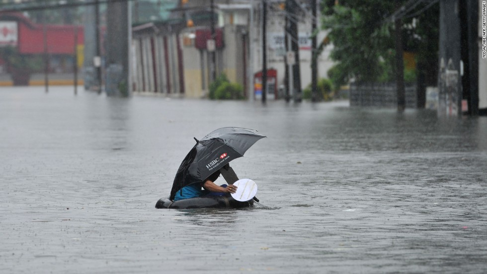 A resident using an inner tube as a makeshift raft paddles through chest-deep floodwaters along a street in Manila on September 23.