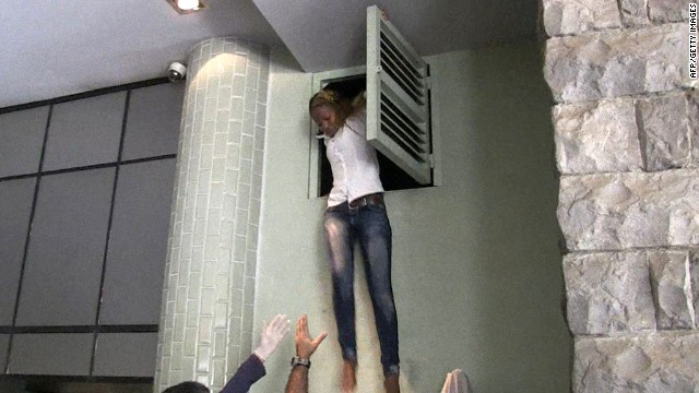 An image grab taken from AFP TV shows a Kenyan woman coming out of an air vent where she was hiding during an attack by masked gunmen at a shopping mall in Nairobi on September 21, 2013.