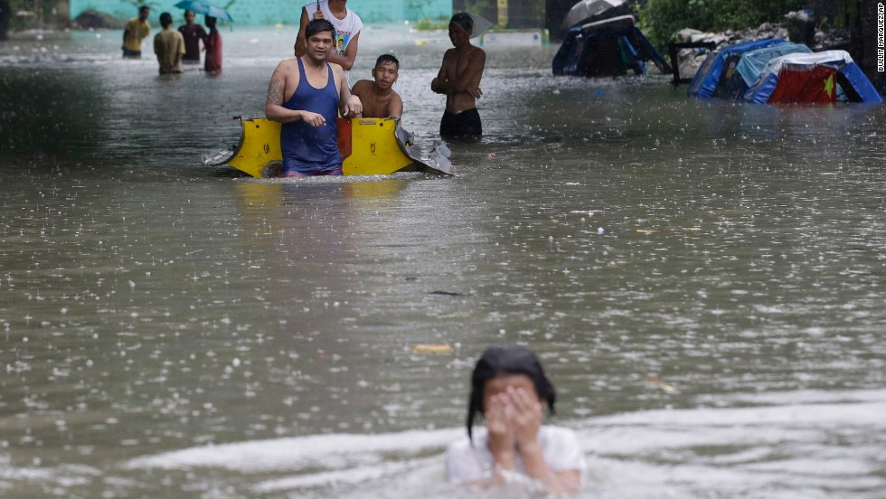 Residents wade through a flooded street in suburban Quezon City, northeast of Manila, on September 23.