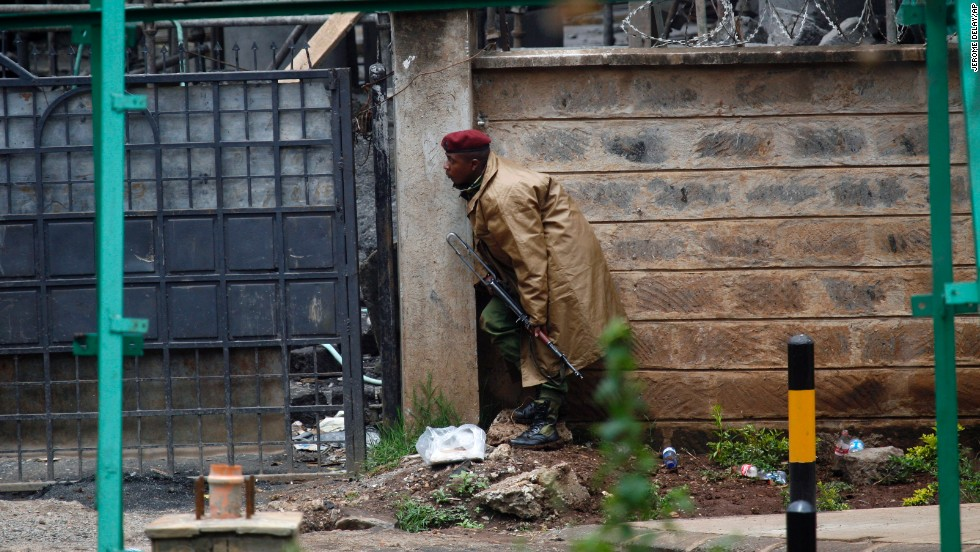 A Kenyan security officer takes cover as gunfire and explosions are heard from the mall on September 23.