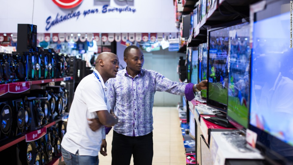 Customers inspect flat-screen televisions for sale.