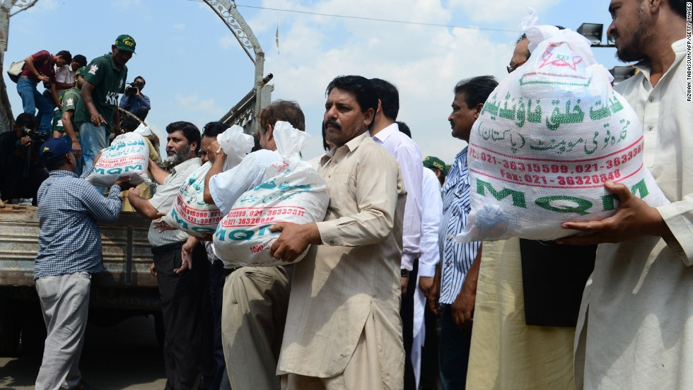 Members of the Pakistani Muttahida Qaumi Movement load relief supplies onto a truck in Karachi on September 25.