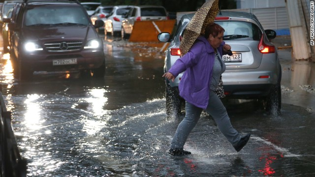 A woman braves the rain in Sochi as severe weather caused chaos in the Russian city.