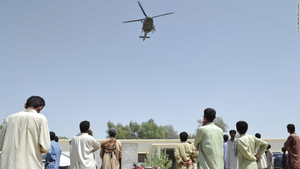 A Pakistani Army helicopter hovers over people as they wait for relief in Awaran on September 26.
