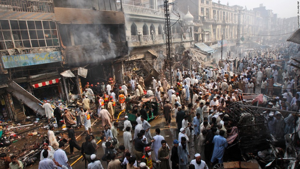 Rescue workers, police officers and civilians gather at the site of a car bomb explosion in Peshawar, Pakistan, on Sunday, September 29. A car loaded with 485 pounds of explosives went off in the city's historic Qissa Khawani bazaar.