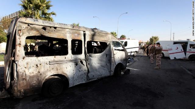 Security forces inspect the site of a car bomb explosion in Iraq's autonomous Kurdistan Region Sunday.
