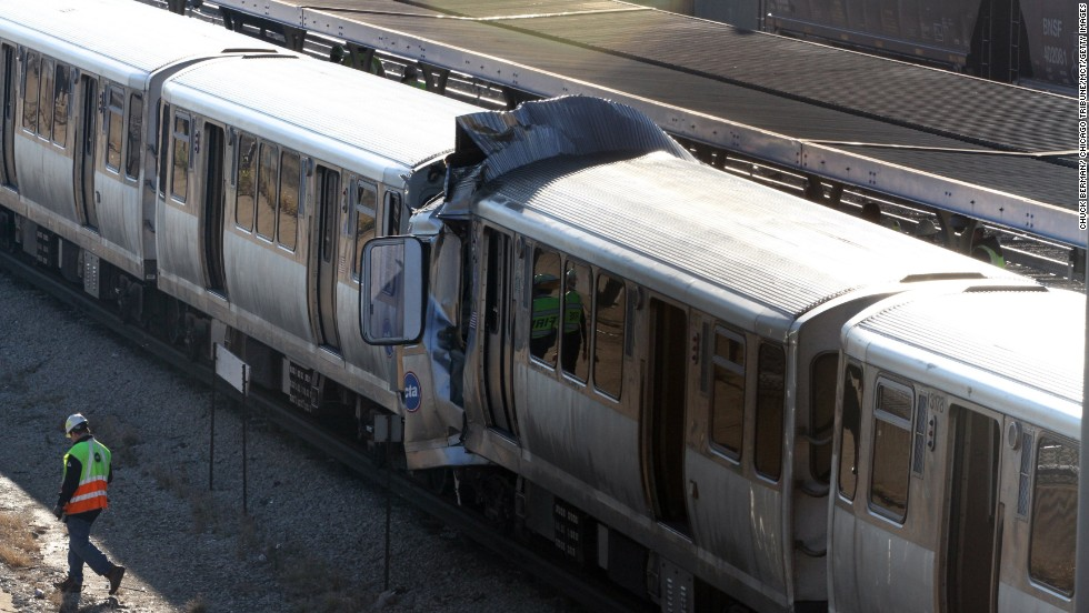 Emergency personnel investigate the scene where a CTA train ran head-on into another train on September 30.