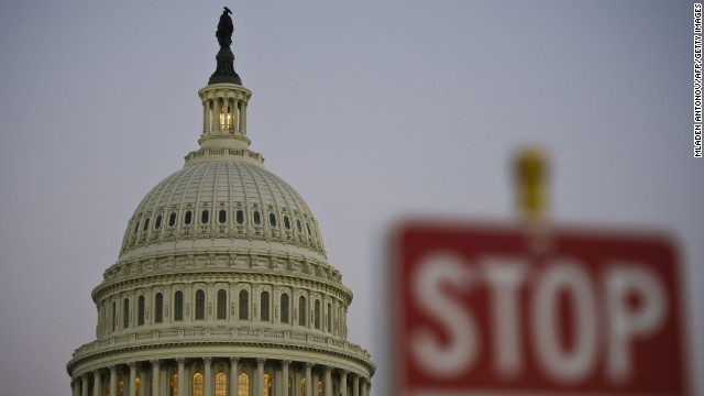 A stop sign is seen at dusk next to the US Congress building on the eve of a possible government shutdown as Congress battles out the budget in Washington, DC, September 30, 2013.