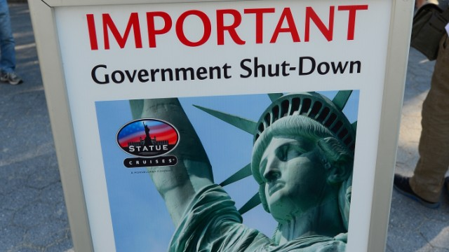 Tourists look at a sign announcing that the Statue of Liberty is closed due to a US government shutdown in New York, October 1, 2013.