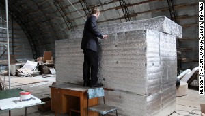 The head of Russian cryonics firm KrioRus, Danila Medvedev, looks inside a liquid nitrogen filled human storage unit