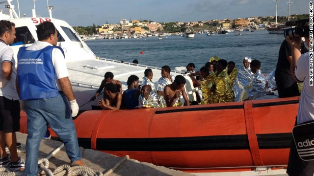 An Italian Coast Guard boat carry rescued migrants as they arrive in the port of Lampedusa Thursday, Oct. 3, 2013. A ship carrying African migrants to Europe caught fire and capsized off the Italian island of Lampedusa on Thursday, killing at least 94 people as it spilled hundreds of passengers into the sea, officials said. Over 150 people were rescued but some 200 others were still unaccounted for.It was one of the deadliest recent accidents in the notoriously perilous Mediterranean Sea crossing from Africa for migrants seeking a new life in the European Union. (AP Photo/Nino Randazzo, Health Care Service, HO)
