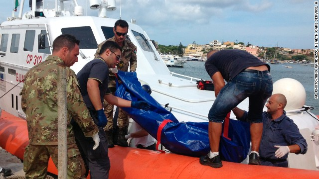 The body of a drowned migrant is unloaded from a Coastguard boat in the port of Lampedusa.