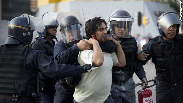Riot police arrest a demonstrator in Mexico City on October 2, 2013. Mexican students marched Wednesday to commemorate the anniversary of the Tlatelolco massacre of university students. AFP PHOTO/ YURI CORTEZ (Photo credit should read YURI CORTEZ/AFP/Getty Images)