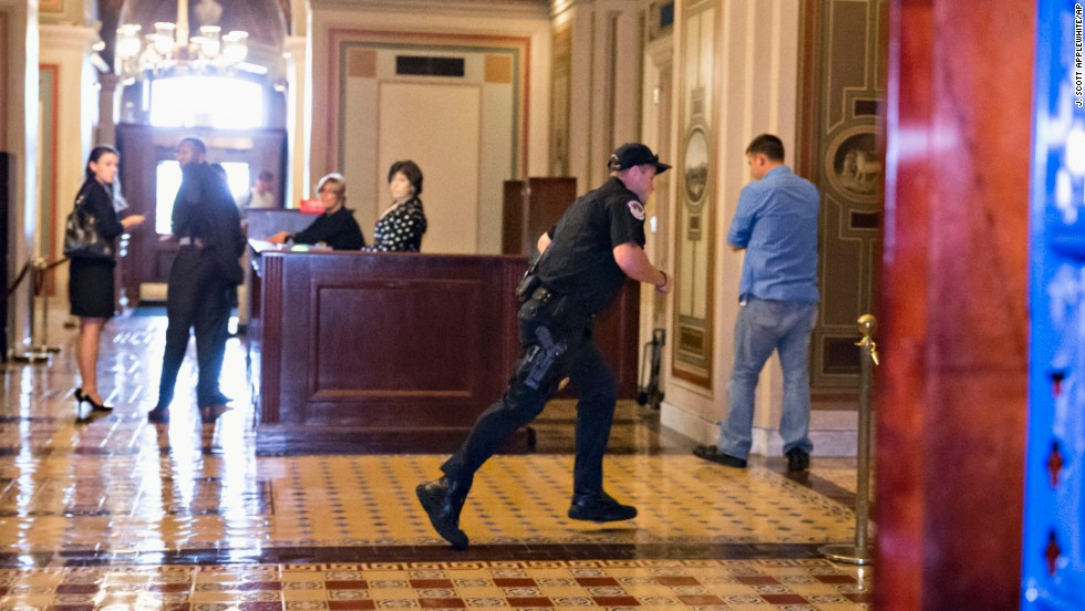 A Capitol Police officer runs through the first-floor lobby in the Senate wing on Capitol Hill.