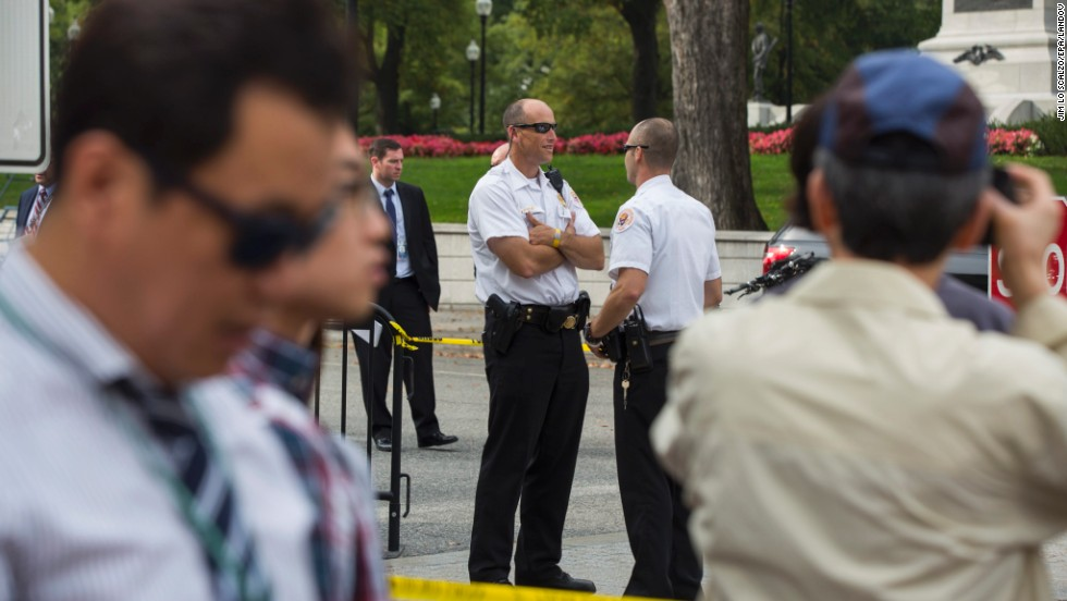 Secret Service agents, as well as other law enforcement officers, gather at the White House entrance.