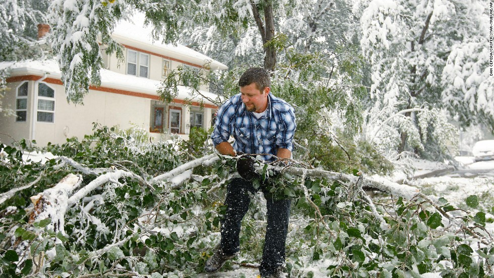 Thomas Leighton clears branches and tree limbs from the street in Casper, Wyoming, on October 4. A major storm dumped heavy, wet snow over Wyoming, bringing down trees and power lines along the way.