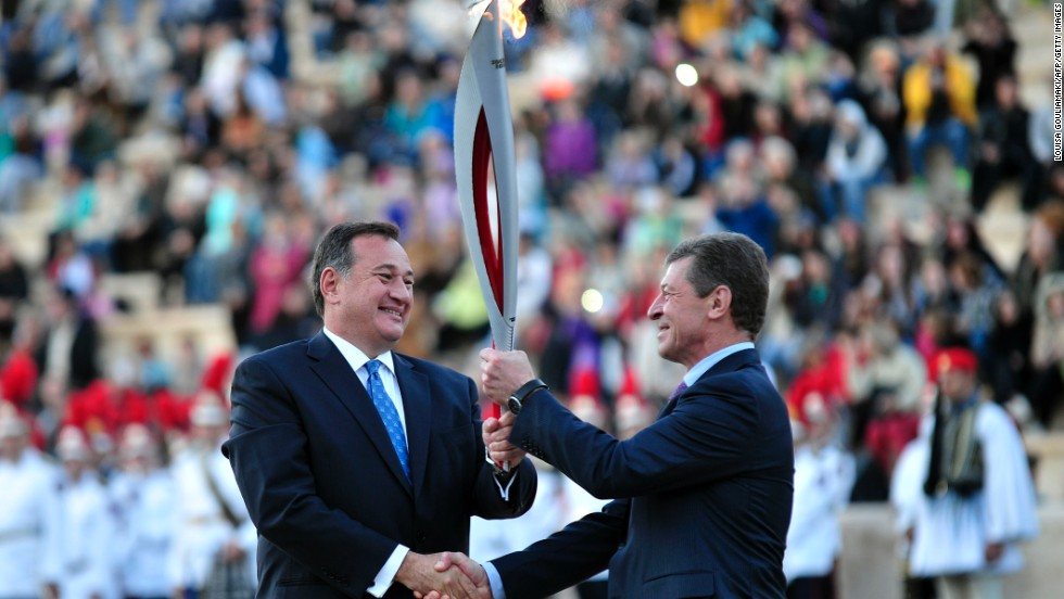 Kapralos (left) hands the flame over to Russia's Deputy Prime Minister Dmitry Kozak ahead of its trip to Moscow, before starting its 65,000-kilometer journey in Sochi on October 7.