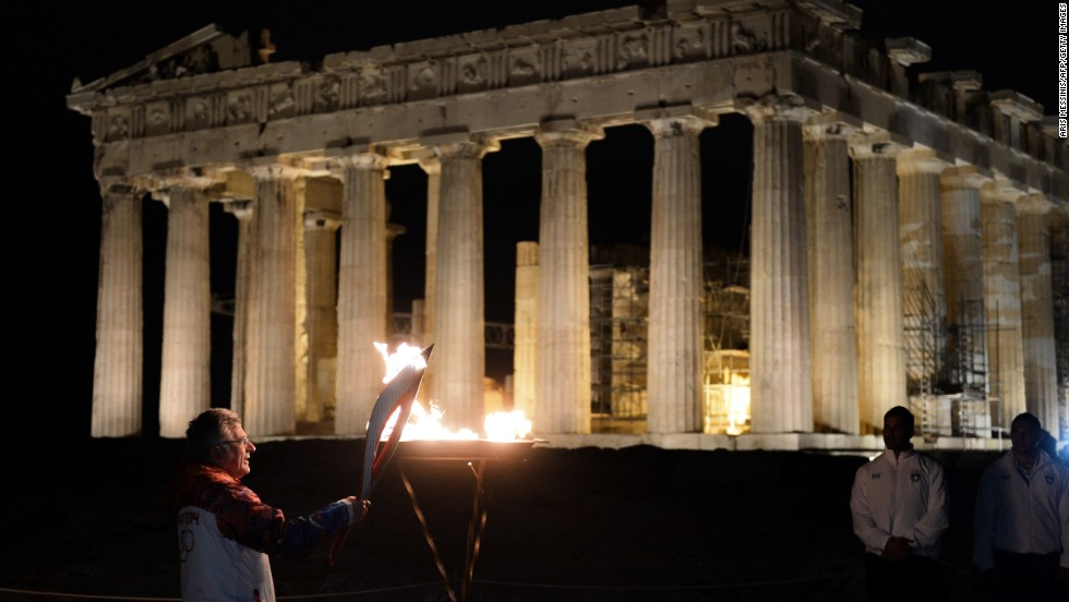 A previous torchbearer, Manolis Katsiadakis the general secretary of Greece's Olympic Committee, lights the flame in front of the ancient Temple of Parthenon on top of the Acropolis hill on October 4.