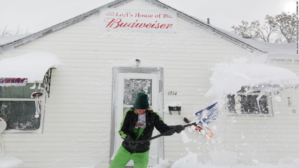 Lori Mehlberg shovels snow to clear a pathway to her home in Rapid City, South Dakota, on October 5. Half the approximately 60,000 residents of Rapid City were without power as of Friday evening, according to Jerry Reichert, a battalion chief with the Rapid City Fire Department.