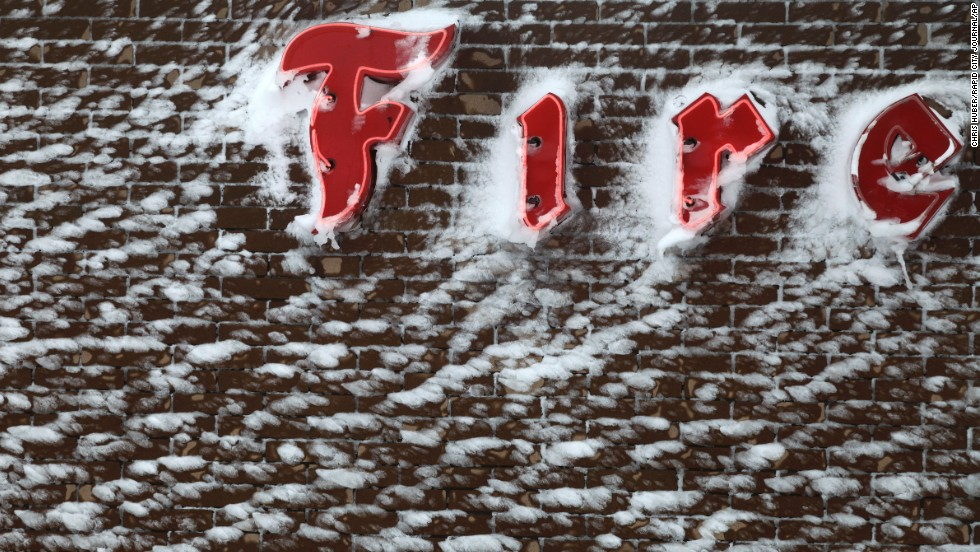 Snow is plastered on to the side of the Firestone sign in downtown Rapid City, South Dakota, on October 5.