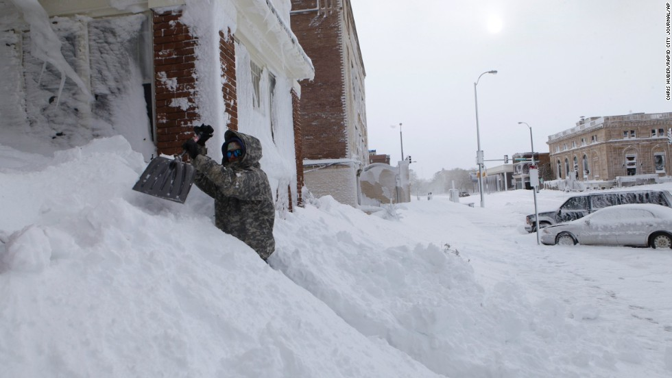 Chad Hoffman clears snow from the entrance to his apartment building in Rapid City, South Dakota, on October 5.