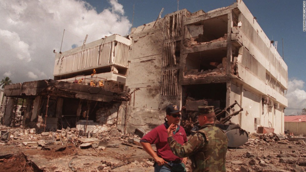 A U.S. Marine talks with an FBI investigator in front of the bomb-damaged U.S. Embassy in Dar es Salaam, Tanzania, on August 15, 1998.