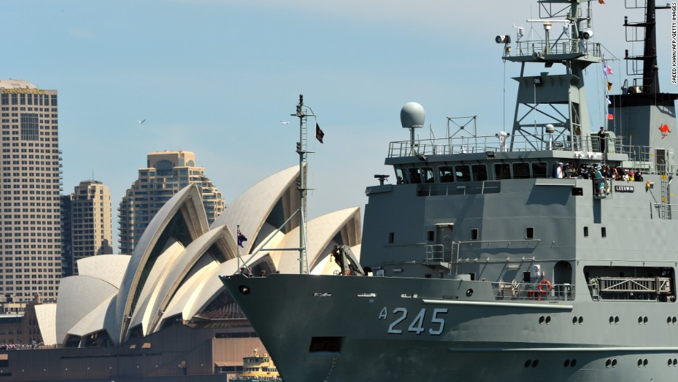 The warship HMAS Leeuwin, carrying Britain's Prince Harry, Australian Prime Minister Tony Abbott and Governor-General Quentin Bryce, passes the opera house on October 5.