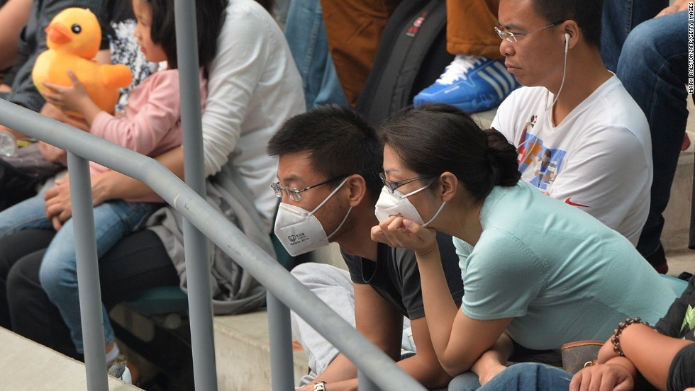 Spectators at the China Open also took to wearing the masks courtside over the weekend, such as this couple watching one of the women's semi-finals Saturday.